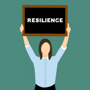 "person hold small board with word ""resilience"" written on it"