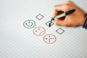 hand checking boxes with smiley face, neutral face, and sad face