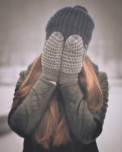 person covering their face with mitten-covered hands
